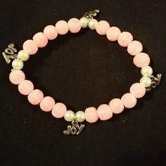 Esta es rosa con perlitas blancas y charms of joy