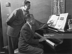 American animator and producer Walt Disney (1901 - 1966) and singer/songwriter Johnny Mercer look over sheet music for 'Song of the South'. Disney stands, looking over Mercer's shoulder while he sits at a piano. A centaur statuette from Disney's 'Fantasia' sits on top of the piano.