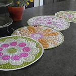 Quilted circles of assorted flowers are made individually and then are attached together with buttons. Can also be used individually as placemats