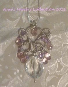This Pendant of Crystal has a very unique Bail. It is a Sterling Silver Wire Wrapped Frame with Light Mystic Pink Quartz Briolettes lined around it and hanging from the middle of it. Violet Swarowski bi cones are scattered throughout the lined Pink Quartz'. A Sterling Silver Chain holds this feminine Victorian Focal.