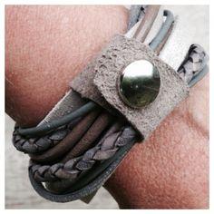 Wikkelarmband die 3x om de pols kan en bij elkaar wordt gehouden door een stukje leer met drukker. Deze armband is in de kleurstelling taupe/grijs.