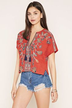 A woven peasant top in a boxy shape with a tasseled deep split neckline, short sleeves, and allover floral embroidery.