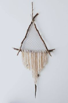 It is a triangular dream catcher made using twigs. Hang some strings and other decorations to create the look.