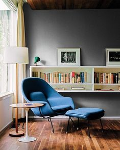 A walnut-topped table and Womb chair, both by Eero Saarinen for Knoll, offer a…