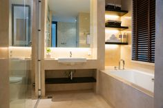 Small, but well laid out modern bathroom with single basin, tub and shower. One end of tub includes built-in shelving with back-lighting providing tub area ambient lighting