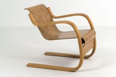"""This armchair is known as the """"spring chair"""". The name is derived from the combined armrest and leg construction. The springs, made of pieces of thin but solid timber, which are glued, assembled and bent in a mould, make the chair flexible and springy. Alvar Aalto, Rocking Chair, School Design, Industrial Design, Armchair, Foundation, Furniture, Architects, Home Decor"""