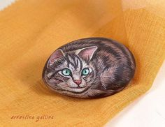 This kitty is a hand painted rock with acrylics on a river stone. Signed by the artist.  size : cm.11 x 6  weight : 400 gr.