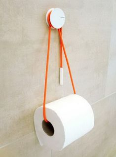 Use a rope to hold your toilet paper storage roll, and add a dash of color to the bathroom. A simple but functional toilet paper storage idea.
