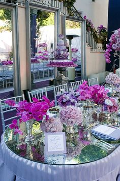 Hot pink orchids and roses in shades of purple perfectly match this wedding's fabulous cake.