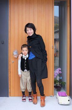 Women fashion: black coat, black shorts, pop of blue shirt, black leggings.