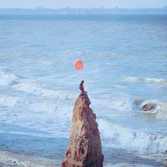 背景が絵のような写真。赤い風船と人魚のような女性が目を引きます。