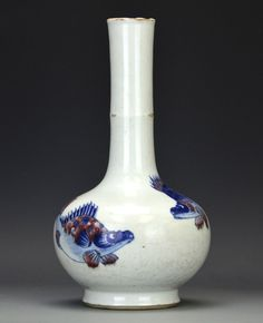 A Chinese 'Fish' Bottle Vase, Kangxi Period, the tall necked globular vase painted in copper red and cobalt blue underglaze to depict three fish encircling the body, the base with cobalt blue double ring, with chips to the glaze at the mouth and neck, appx. 9 5/8 in. H.