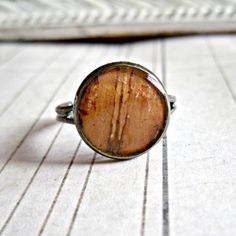 Very unusual use of materials; a piece of birch bark is encased in resin and a vintage band making a unique ring.