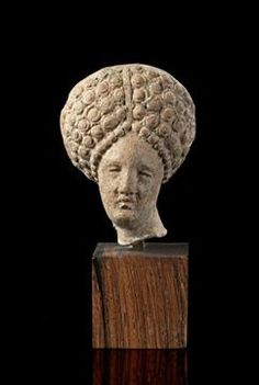 Lot 554 - Terracotta head of a young woman with elaborate hairdress. Greek, 4th century B.C. Broken at the