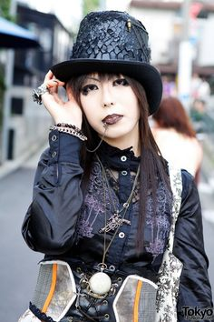 22-year-old Kurosan on the street in Harajuku. She's a big fan of the Japanese rock band Dir en Grey. Most of what she's wearing comes from her favorite shop, h.NAOTO: the lace shirt, corset belt, layered maxi skirt, scales hat, tote bag, a chain that runs between her earring and lip piercings, a silver armor ring, a pocket watch necklace, and various other pieces of gothic jewelry. Her double strap platform high heeled shoes are from Queen Bee.