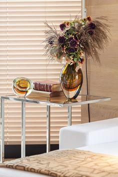 Decoração com parede revestida de madeira, sofá branco e mesa lateral com vaso de vidro com flores e livros.