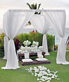 Interesting wedding canopy with cushions and white draperies for an outdoor…