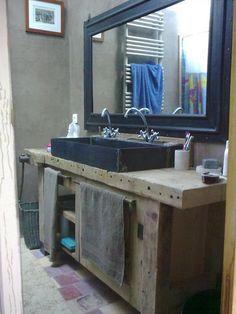 Un établi transformé en meuble de salle de bain avec vasque en pierre...