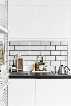 white Scandinavian style kitchen, white tiles with black grout