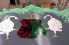 In this picture we have finished painting the shield. We have chosen to paint the background with bright colors, so that it would stand out more. We have chosen red an green because they are complementary colors. We also started to paint the crown.