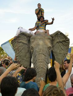 Players of Hindu Club celebrate riding a plastic elephant
