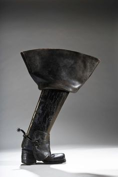 """English, turn of the 18th century""""As the 17th century  Leather-covered heels suggested refinement, while stacked leather connoted action and were commonly found on men's riding boots. This 'thigh' boot features a high, stacked-leather heel and was clearly designed to be worn in harsh riding conditions, such as battle. The use of hard, thick, 'jack' leather provided a great deal of protection, while the stacked leather heel would have kept the rider's foot in the stirrup."""""""