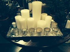 Tray of taller white candles with small mercury glass votives around the edges Photo taken at Pottery Barn store