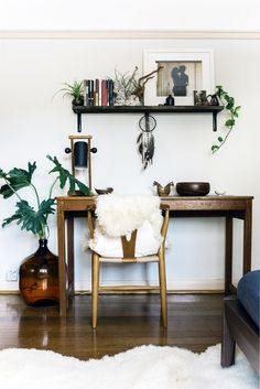 Home office space with a wishbone chair, lamb throws, and indoor plants