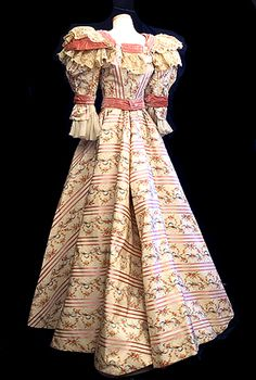 This aristocratic two-piece gown (c1895) is fashioned from luxurious silk faille that combines ribbon-weave satin stripes with watered silk flowers. This expensive textile is embellished with pink velvet trim and flounces of beige lace and ivory silk chiffon. Both pieces are lined with ivory taffeta.