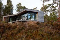 Terrengtilpasset: Glassfeltene i den langstrakte bygningskroppen reflekterer skogen og himmelen. Platekledningen er i kryssfiner, poppelplater beiset svart med tre strøk.