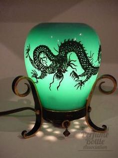 DeVilbiss Dragon Motif electric perfume lamp from 1924.  An indentation  in the top of the shade holds the fragrance.   Black design on jade green glass.