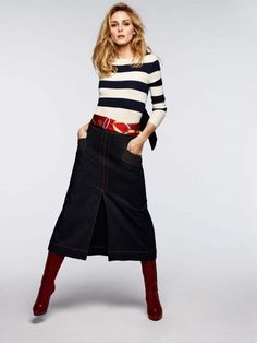 Olivia Palermo wears a striped sweater, denim midi skirt, scarf belt, and knee-high boots