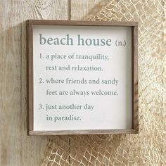 """Our Beach House Sign is the perfect accessory for your home or summer home. The sign features a wood plaque with raised thick wood border and a printed beach house """"definition."""" Arrives with saw tooth"""