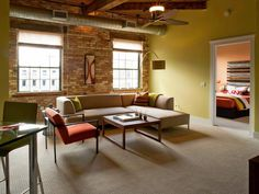 Warm exposed brick and ductwork and original wood ceilings are softened by a soothing green color palette in this loft space. Orange accents add just enough vibrancy. Design by HGTV Star contestant Tylor Devereaux