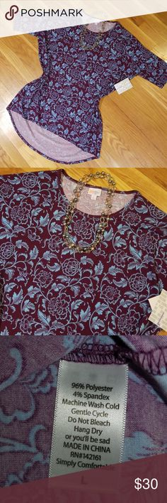 """NWT LuLaRoe Irma, sz L Brand new with tags! LuLaRoe Irma tunic. Gorgeous deep purple (almost maroon) background with light blue floral print. I'd bought thinking the print was a different color so unfortunately it doesn't match the skirt I needed it to go with. My loss, your gain! Measurements laying flat: 28"""" bust, 29.5"""" length in front, 34.5"""" length in back. LuLaRoe Tops Tees - Short Sleeve"""