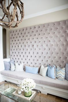 Tufted wall and bench provide smart seating for the living room [Design: Steele Street Studios]