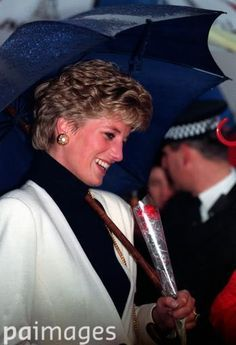 January 13, 1993 The Princess Diana clutches a red rose given to her as she takes shelter under an umbrella during a walkabout at the Royal Preston Hospital, Lancashire, after she had opened its magnetic resonance imaging scanner unit.