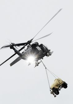 An UH-60L Blackhawk helicopter carries a water trailer away as Soldiers from the Forward Support Company, 6th Engineer Battalion, conduct slingload operations with the 1st Battalion, 207th Aviation Regiment, Alaska Army National Guard, at Landing Zone Ranger, JBER-Richardson, September 20, 2012.