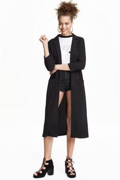 Casaco comprido : Casaco comprido em tecido com textura. Tem mangas a 3/4 com dobra cosida na extremidade e bolsos na frente. Sem botões. Sem forro.