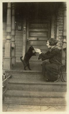 vintage photograph of a lady on the porch with her black feline