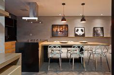 Uma ilha central integra o estar com uma mesa de jantar grande, que complementa o espaço de receber.