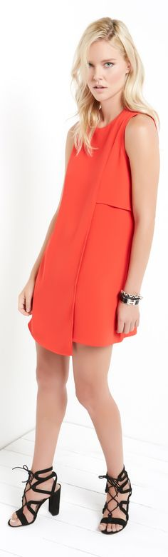 An asymmetric cut creates a dimensional look on a crepe shift dress with a clean, minimalist aesthetic.