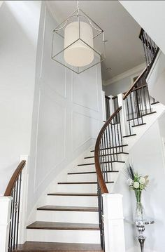 Elegant entrance features a cage lantern illuminating a curved staircase with wainscoting and a wood banister with iron spindles.