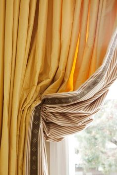 Drapes dont need to be lined with white! These sunny drapes have an unexpected striped lining and coordinating tape on the leading edge. You only notice those surprise details when the drapes are tied back.