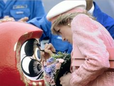1986-05-12 Diana inks an eye to a Daruma doll, a symbol of good luck, during a visit to the Nissan Motor Plant in Zama, South of Tokyo