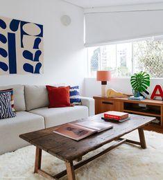 Sala de TV tem sofá bege com almofadas nas cores azul e ocre, painel de tecido e mesa de centro de madeira.