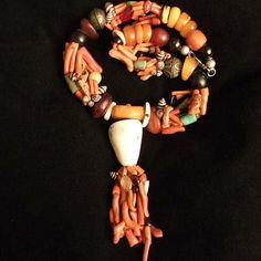 Africa | A Moroccan Berber necklace which has all of the best ingredients, wonderful old amber, 6 strands of irregular shaped coral beads, green and black amazonite beads, small striped shells, two metal beads and finished with two silk braided strands of cords with silver colored sequins and beautifully woven knots on each end. | This is an authentic necklace with its original stringing but is sturdy enough to wear. | 2400$