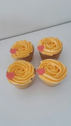 Yellow icing cupcakes with pink hearts.