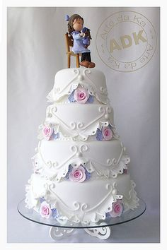 White cake with little pink roses and an eyelet look in the decoration