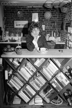 Author Laurie Colwin in the kitchen of her home, leaning on a bookcase of cookbooks, 1978   via Corbis via Book Patrol